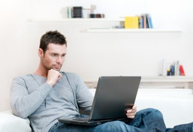 Young man working absorbed on laptop at home copy space